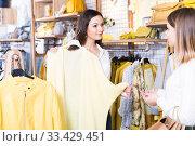 Купить «Female seller showing yellow sweater to client in the modern shop», фото № 33429451, снято 15 марта 2018 г. (c) Яков Филимонов / Фотобанк Лори