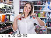 Купить «girl holding assortment nail polishes», фото № 33429483, снято 31 января 2018 г. (c) Яков Филимонов / Фотобанк Лори