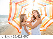 Купить «Mom with a small daughter walks along the beach with an umbrella on a sunny summer day.», фото № 33429607, снято 18 июля 2019 г. (c) Акиньшин Владимир / Фотобанк Лори