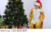 Девочка притащила коробку и села у новогодней елки. Стоковое видео, видеограф Иванов Алексей / Фотобанк Лори