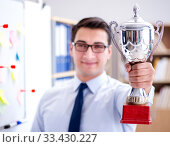 Young businessman receiving prize cup in office. Стоковое фото, фотограф Elnur / Фотобанк Лори
