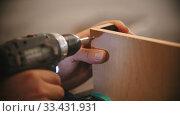 Купить «Carpentry working - man worker drills screws into the plywood», видеоролик № 33431931, снято 2 июня 2020 г. (c) Константин Шишкин / Фотобанк Лори
