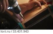 Купить «Carpentry industry - man worker drills screws into the piece of plywood in the workshop», видеоролик № 33431943, снято 27 мая 2020 г. (c) Константин Шишкин / Фотобанк Лори