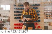 Купить «Carpentry industry - man worker choosing screws from the stand and walks away», видеоролик № 33431967, снято 2 июня 2020 г. (c) Константин Шишкин / Фотобанк Лори
