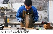 Concrete workshop - a man putting a mold on a concrete product. Стоковое видео, видеограф Константин Шишкин / Фотобанк Лори