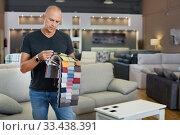 Купить «Client choosing upholstery fabric from catalog with samples», фото № 33438391, снято 29 октября 2018 г. (c) Яков Филимонов / Фотобанк Лори