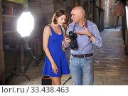 Купить «Photographer showing photos on camera to model girl», фото № 33438463, снято 5 октября 2018 г. (c) Яков Филимонов / Фотобанк Лори