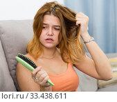 Купить «Young woman is nervous because her hair suffers from avitaminosis», фото № 33438611, снято 5 августа 2020 г. (c) Яков Филимонов / Фотобанк Лори
