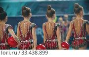 Купить «RUSSIA, KAZAN 12-03-2020, Kazan Stars Open: Young women in colorful bright costumes walking out from the stage of the rhythmic gymnastics tournament and holding balls», видеоролик № 33438899, снято 27 мая 2020 г. (c) Константин Шишкин / Фотобанк Лори