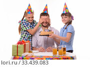 Купить «Дети закрыли глаза папе и подготовили для него сюрприз в виде торта со свечками», фото № 33439083, снято 9 марта 2020 г. (c) Иванов Алексей / Фотобанк Лори
