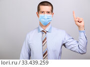Купить «Man in shirt and medical mask shows finger in up, isolated», фото № 33439259, снято 26 марта 2020 г. (c) Владимир Арсентьев / Фотобанк Лори
