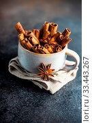Купить «Cup of cinnamon sticks and anise star - spices for mulled wine cooking on dark stone background with copy space», фото № 33443267, снято 9 апреля 2020 г. (c) age Fotostock / Фотобанк Лори