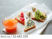 Купить «Sandwiches with avocado, cheese and glass of orange juice for having snack or break over white cooking paper. Food concept.», фото № 33443335, снято 30 мая 2020 г. (c) easy Fotostock / Фотобанк Лори