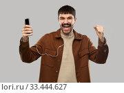 Купить «smiling young man with earphones and smartphone», фото № 33444627, снято 22 февраля 2020 г. (c) Syda Productions / Фотобанк Лори