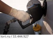 Купить «Профилактические меры во время эпидемии вируса. Рука в латексной перчатке держит заправочный пистолет», фото № 33444927, снято 25 марта 2020 г. (c) Ирина Кожемякина / Фотобанк Лори