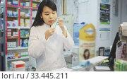 Купить «Chinese woman pharmacist in protective facial mask standing with arms crossed in interior of pharmacy», видеоролик № 33445211, снято 2 апреля 2020 г. (c) Яков Филимонов / Фотобанк Лори