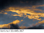 Thunderstorm clouds illuminated by disappearing rays at sunset, thunderclouds floating across sunny blue sky to change season weather. Стоковое фото, фотограф А. А. Пирагис / Фотобанк Лори