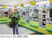 Покупательница в аптеке считает деньги (2020 год). Редакционное фото, фотограф Victoria Demidova / Фотобанк Лори