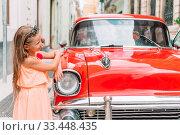 Купить «Tourist girl in popular area in Havana, Cuba. Young kid traveler smiling», фото № 33448435, снято 13 апреля 2017 г. (c) Дмитрий Травников / Фотобанк Лори