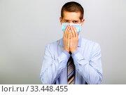 Купить «A business man in a mask grabbed his face with his hands», фото № 33448455, снято 26 марта 2020 г. (c) Владимир Арсентьев / Фотобанк Лори