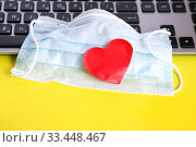 Купить «Blue cloth medical mask with heart on computer keyboard. Home schooling and working from home during quarantine.», фото № 33448467, снято 25 марта 2020 г. (c) Papoyan Irina / Фотобанк Лори