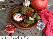 Купить «Dolma in a clay plate with pomegranate, sour cream and chacha on a wooden background», фото № 33448915, снято 23 марта 2020 г. (c) Марина Володько / Фотобанк Лори