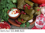 Купить «Dolma in a clay plate with pomegranate, sour cream and chacha on a wooden background», фото № 33448923, снято 23 марта 2020 г. (c) Марина Володько / Фотобанк Лори