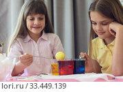 Купить «Дети красят пасхальные яйца в стаканах с жидким красителем», фото № 33449139, снято 28 марта 2020 г. (c) Иванов Алексей / Фотобанк Лори