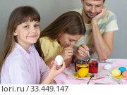 Купить «Девочка с яйцом в руках посмотрела в кадр, на дальнем плане семья красит яйца в стаканах с красителями», фото № 33449147, снято 28 марта 2020 г. (c) Иванов Алексей / Фотобанк Лори
