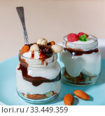 Купить «Sweet tasty milk curd creamy food in a glass jar of homemade breakfast. Cheesecake, English Trifle, Eton dessert, tiramisu, zuppa Inglese with nuts, almonds, cashews, hazelnuts, candied fruits and chocolate sauce», фото № 33449359, снято 14 декабря 2019 г. (c) Светлана Евграфова / Фотобанк Лори