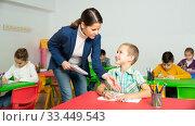 Купить «Friendly teacher woman helping boy during lesson in schoolroom», фото № 33449543, снято 29 мая 2020 г. (c) Яков Филимонов / Фотобанк Лори