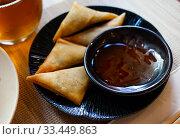 Купить «Potato curry samosas served with sause at plate», фото № 33449863, снято 30 мая 2020 г. (c) Яков Филимонов / Фотобанк Лори