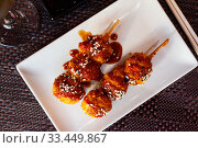 Купить «Chicken balls in spicy sauce with sesame seeds on a skewer. Japanese cuisine», фото № 33449867, снято 9 апреля 2020 г. (c) Яков Филимонов / Фотобанк Лори