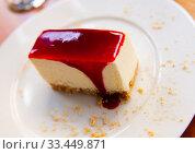 Купить «Slice of delicious classical cheesecake with fruity sauce served in cafeteria», фото № 33449871, снято 6 июля 2020 г. (c) Яков Филимонов / Фотобанк Лори
