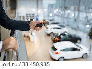 Купить «Man with keys from his transport in car dealership», фото № 33450935, снято 15 декабря 2019 г. (c) Tryapitsyn Sergiy / Фотобанк Лори