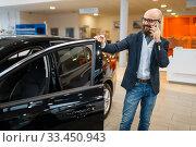 Купить «Man talks by mobile phone in car dealership», фото № 33450943, снято 15 декабря 2019 г. (c) Tryapitsyn Sergiy / Фотобанк Лори