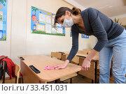 Девушка в медицинской маске моет парты в школе в период карантина. Редакционное фото, фотограф Иванов Алексей / Фотобанк Лори
