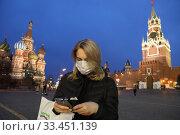 Молодая девушка в защитной маске на Красной площади во время эпидемии коронавируса в Москве (2020 год). Редакционное фото, фотограф Дмитрий Неумоин / Фотобанк Лори