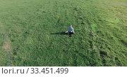 Купить «Low orbital flight around man on green grass with notebook pad at yellow rural field.», видеоролик № 33451499, снято 13 марта 2019 г. (c) Александр Маркин / Фотобанк Лори