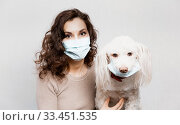 Woman in protective surgical mask holds dog pet in face mask. Coronavirus disease COVID-19 is dangerous for pets. Girl in medical mask and dog in protective mask. Coronavirus pandemic Precautions. Стоковое фото, фотограф Сергей Тимофеев / Фотобанк Лори