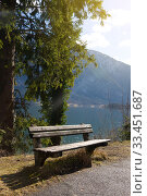 Empty wooden bench on shore of beuatiful lake in austrian Alps. Winter sunny morning on lake Hallstatt. The most beautiful lake to explore in Austria. Стоковое фото, фотограф Papoyan Irina / Фотобанк Лори