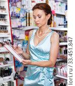 Купить «Woman with schemes of nail polish in cosmetics shop», фото № 33451847, снято 21 июня 2018 г. (c) Яков Филимонов / Фотобанк Лори