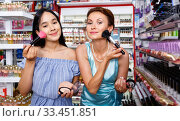 Attractive young girl and female testing face powder at cosmetics store. Стоковое фото, фотограф Яков Филимонов / Фотобанк Лори