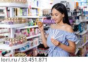 Купить «Girl with testers in perfumery, choosing perfume in cosmetic shop», фото № 33451871, снято 21 июня 2018 г. (c) Яков Филимонов / Фотобанк Лори