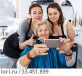 Купить «Hairdressers wit senior woman client making selfie», фото № 33451899, снято 26 июня 2018 г. (c) Яков Филимонов / Фотобанк Лори