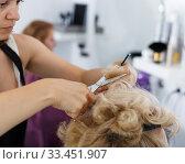 Купить «Hands of hairdresser making hairstyle for female», фото № 33451907, снято 26 июня 2018 г. (c) Яков Филимонов / Фотобанк Лори