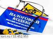 Купить «Очки , Налоговый кодекс и международный знак биологической опасности», фото № 33452951, снято 30 марта 2020 г. (c) Николай Винокуров / Фотобанк Лори