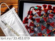 Очки, медицинская маска, градусник и планшет с открытым сайтом Википедии на странице с информацией об эпидемии коронавируса COVID-19 и изображением вируса под микроскопом. Редакционное фото, фотограф Николай Винокуров / Фотобанк Лори