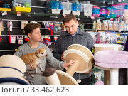 Father with teenager son and little dog choose products for cats in petshop. Стоковое фото, фотограф Яков Филимонов / Фотобанк Лори