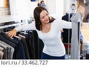 Купить «Smiling female choosing fashion sweater in the boutique», фото № 33462727, снято 17 января 2018 г. (c) Яков Филимонов / Фотобанк Лори